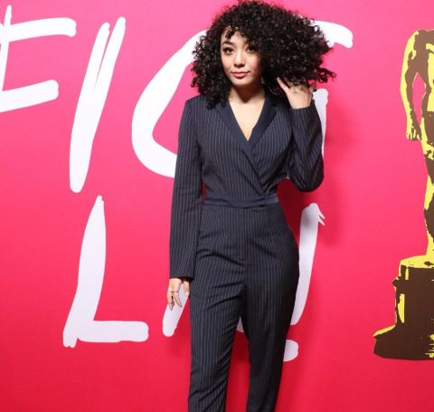 Elyfer Torres wearing black suit and pants infront of a red FICG wallpaper.