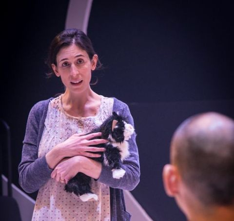 Cara Mantella with a cute cat in her hand in a theater.