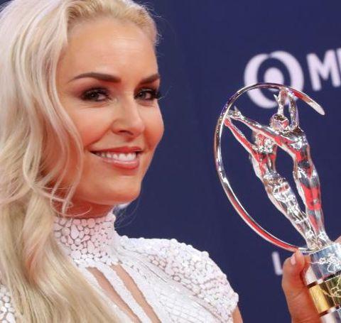 Lindsey Vonn in white dress poses alongside a trophy.