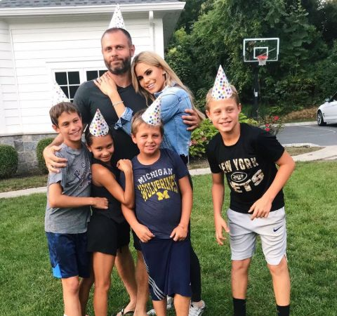 Jackie Goldschneider in blue poses alongside husband Evan Goldschneider and her four children.