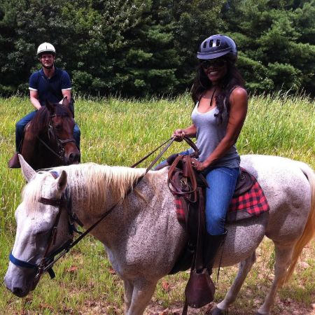 Bradford Sharp and his wife riding horse on a vacation