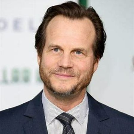 Late Bill Paxton posing for a photo at an event.