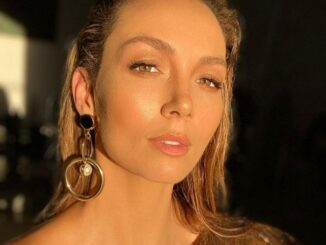 Ricki-Lee Coulter wearing a golden dress and posing for a photo.
